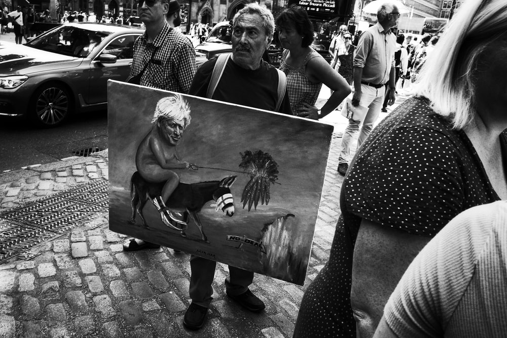 grayscale photo of man holding painting