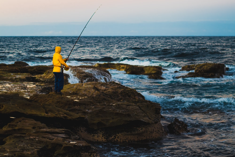 person in yellow hoodie fishing during daytime