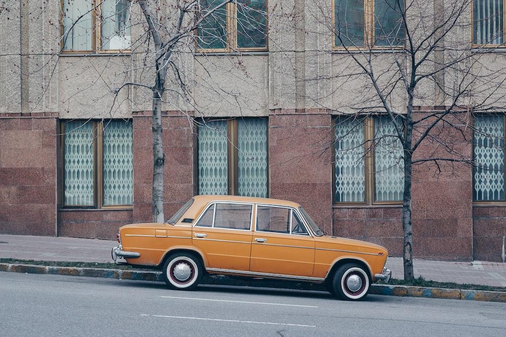 orange sedan on road