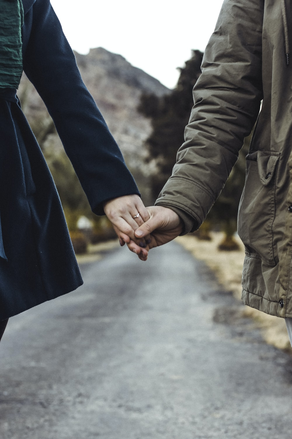 two person holding hands while walking on asphalt road