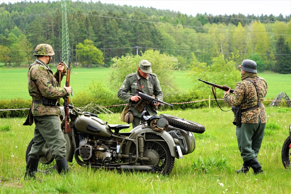 men holding rifles standing beside motorcycle with sidecar