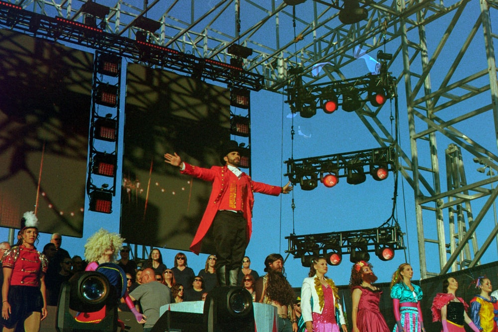 man in red coat standing in front of crowd