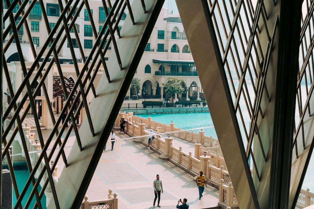 people walking on bridge beside pool in front of building