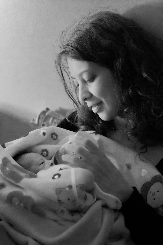woman feeding baby through feeding bottle