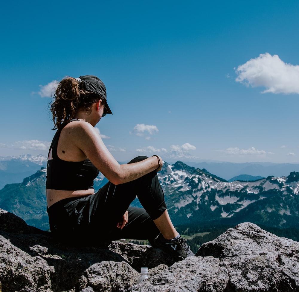 woman in black sports bra sitting on rock formation