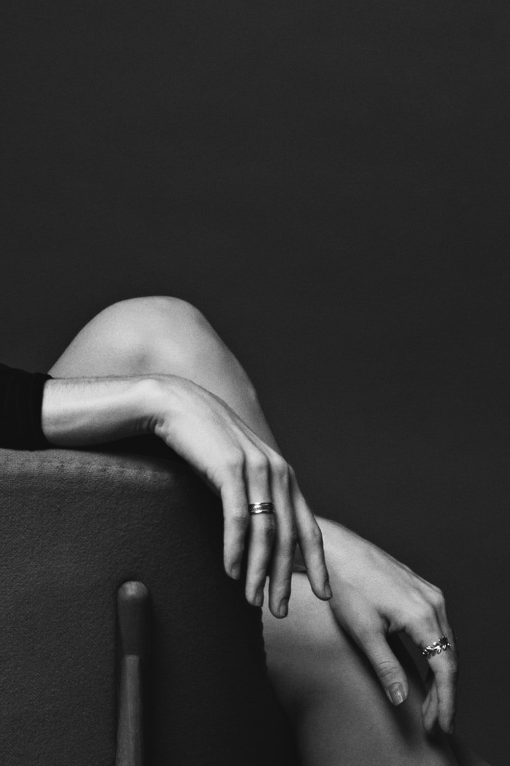 grayscale photography of sitting person wearing rings with both hands
