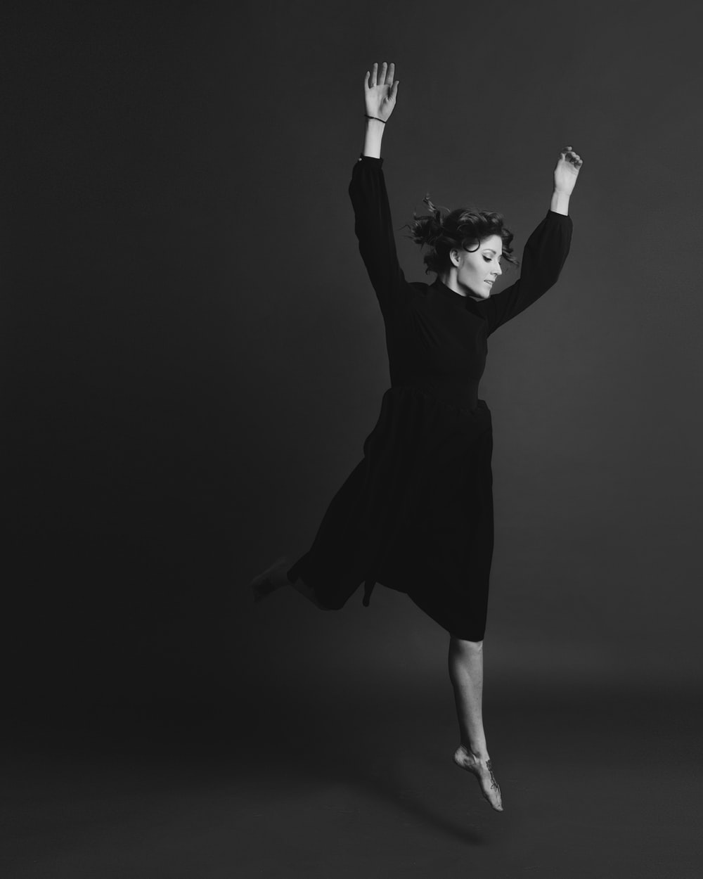 grayscale photography of woman wearing long-sleeved dress