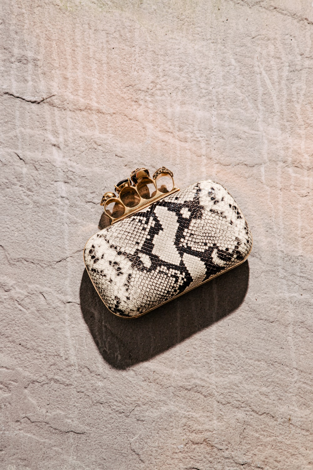white and black snakeskin leather pouch on gray surface