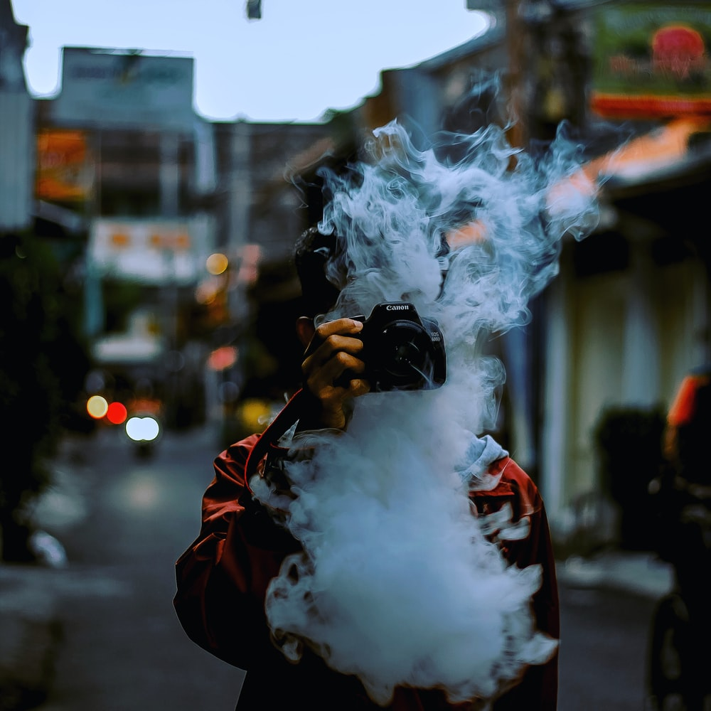 man breathing smoke and holding Canon camera covering his face