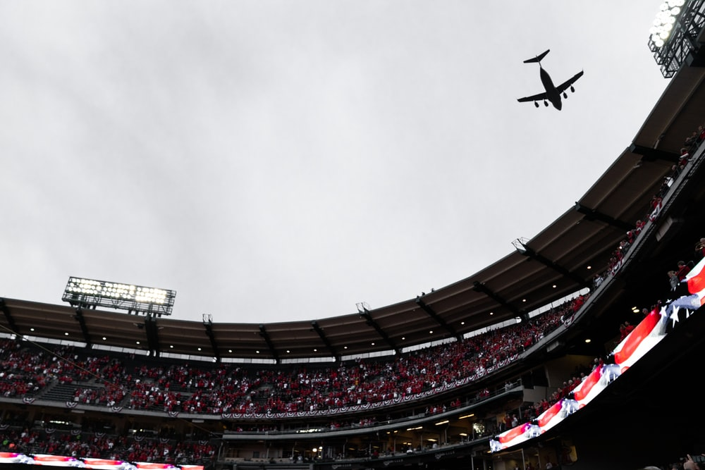airplane flying above stadium
