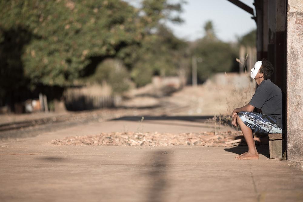 man wearing mask sitting on bench