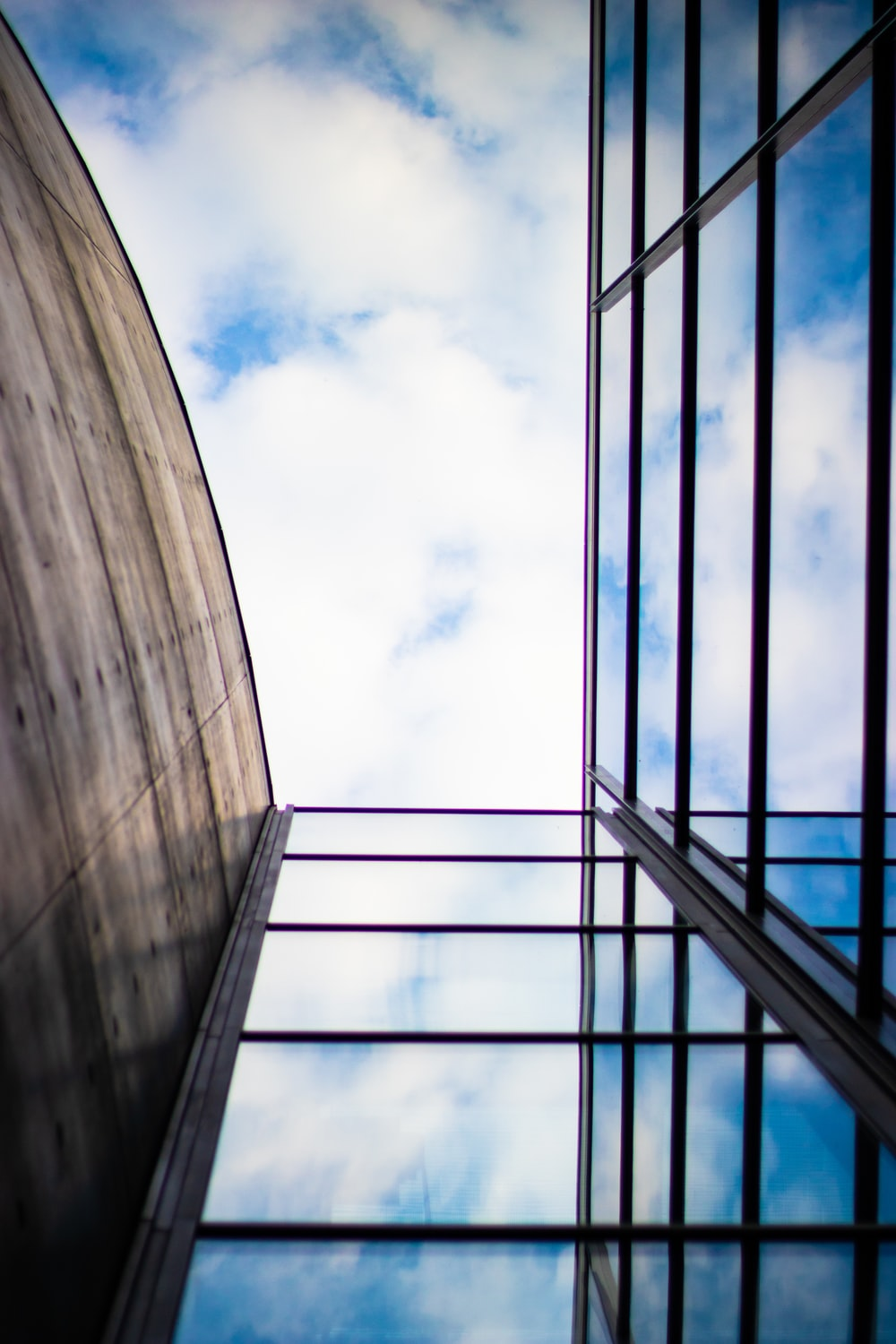 low-angle photography of building under white clouds and blue sky