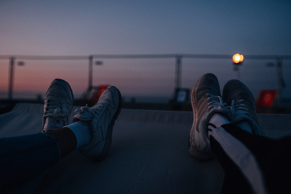 two persons resting their feet on white surface