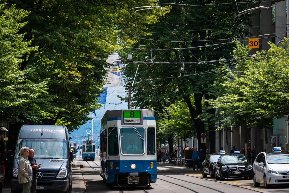 tram passing by several vehicles