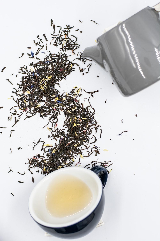 black ceramic teacup on white surface