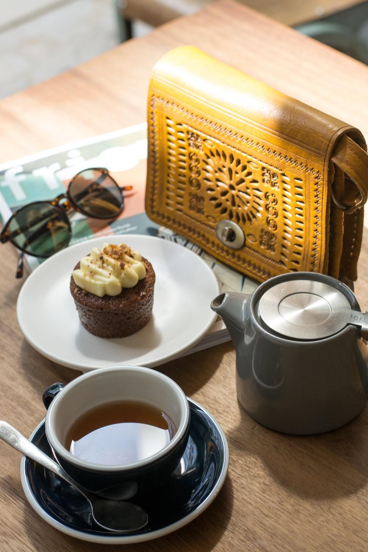 black teacup with tea beside cupcake