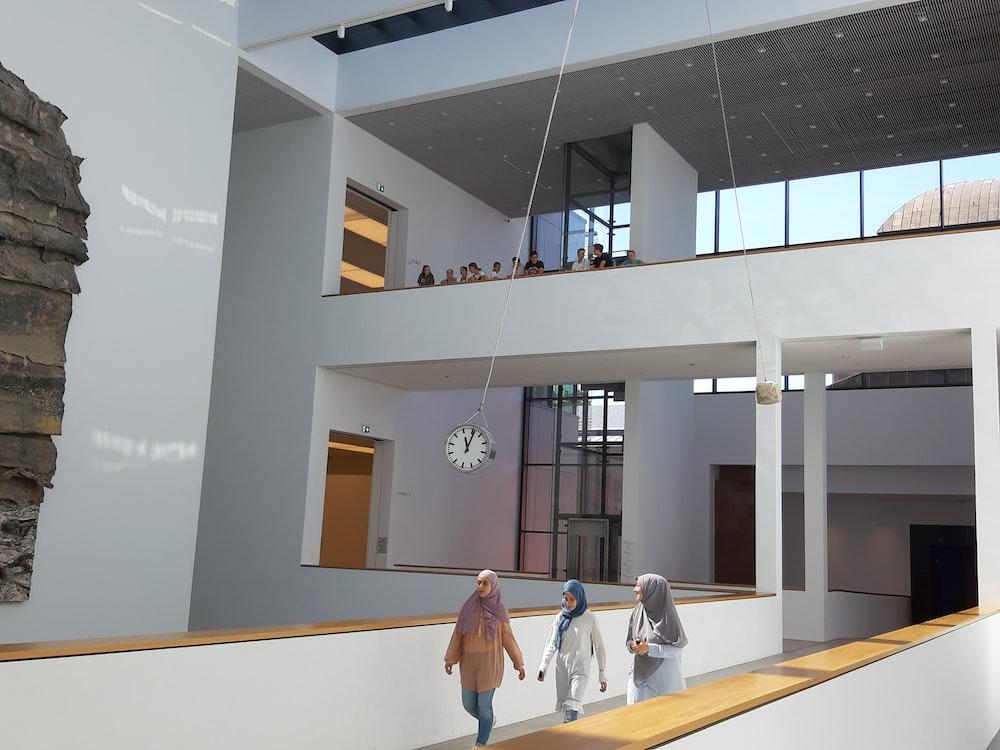 three women walking inside concrete building