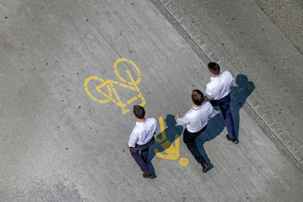 three men wearing white dress shirt and black dress pants walking side by side