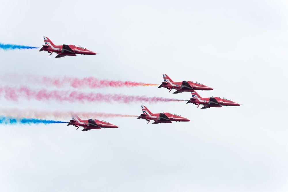 five pink planes with teal and pink smokes