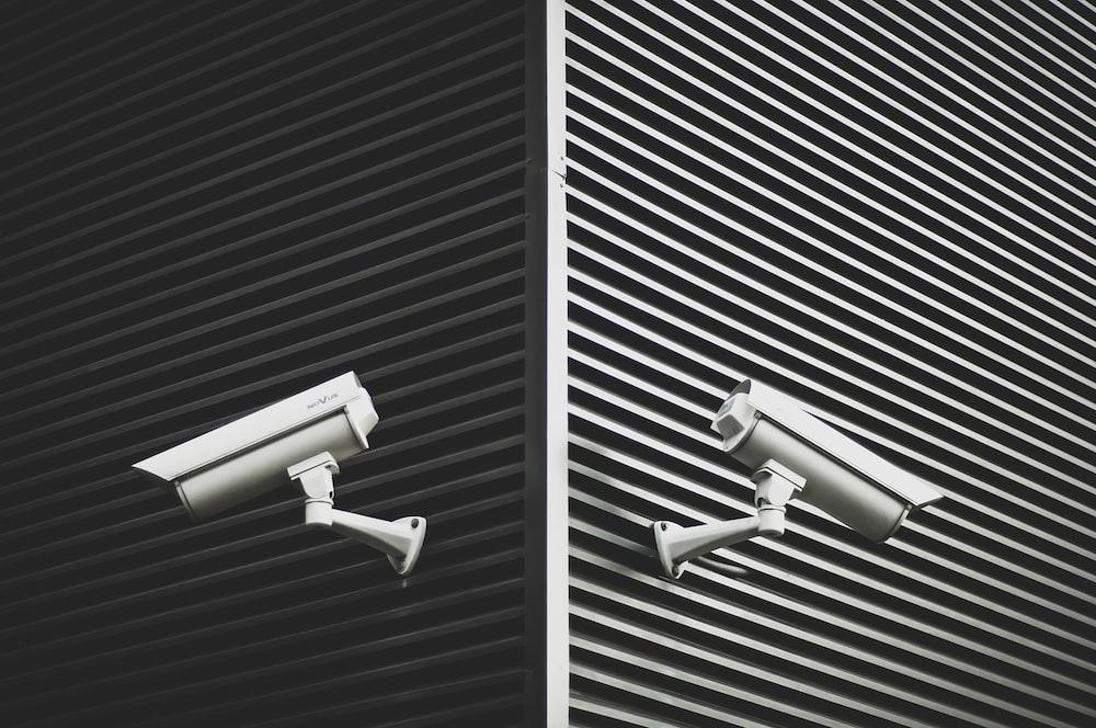 two grey CCTV cameras