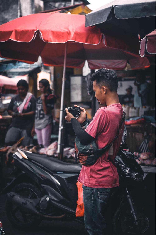 shallow focus photo of man using black DSLR camera