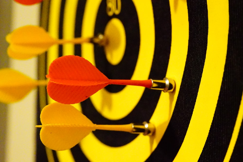 black and yellow dartboard with magnet darts
