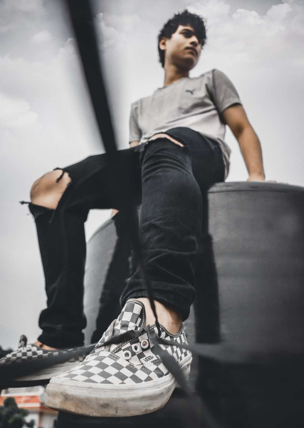 man wearing distressed black denim jeans close-up photography