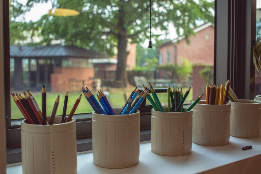 five cylindrical white ceramic pencil containers