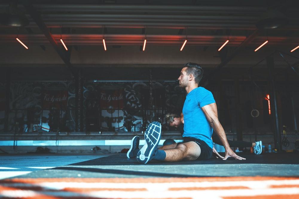 man sitting on exercise mat