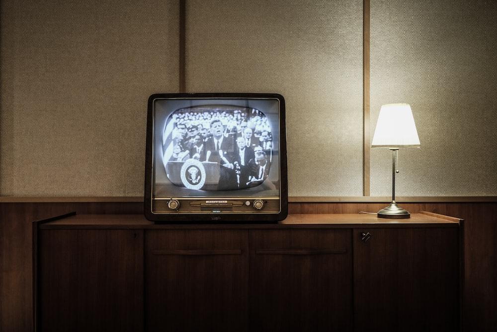 vintage black CRT TV turned-on near lighted table lamp
