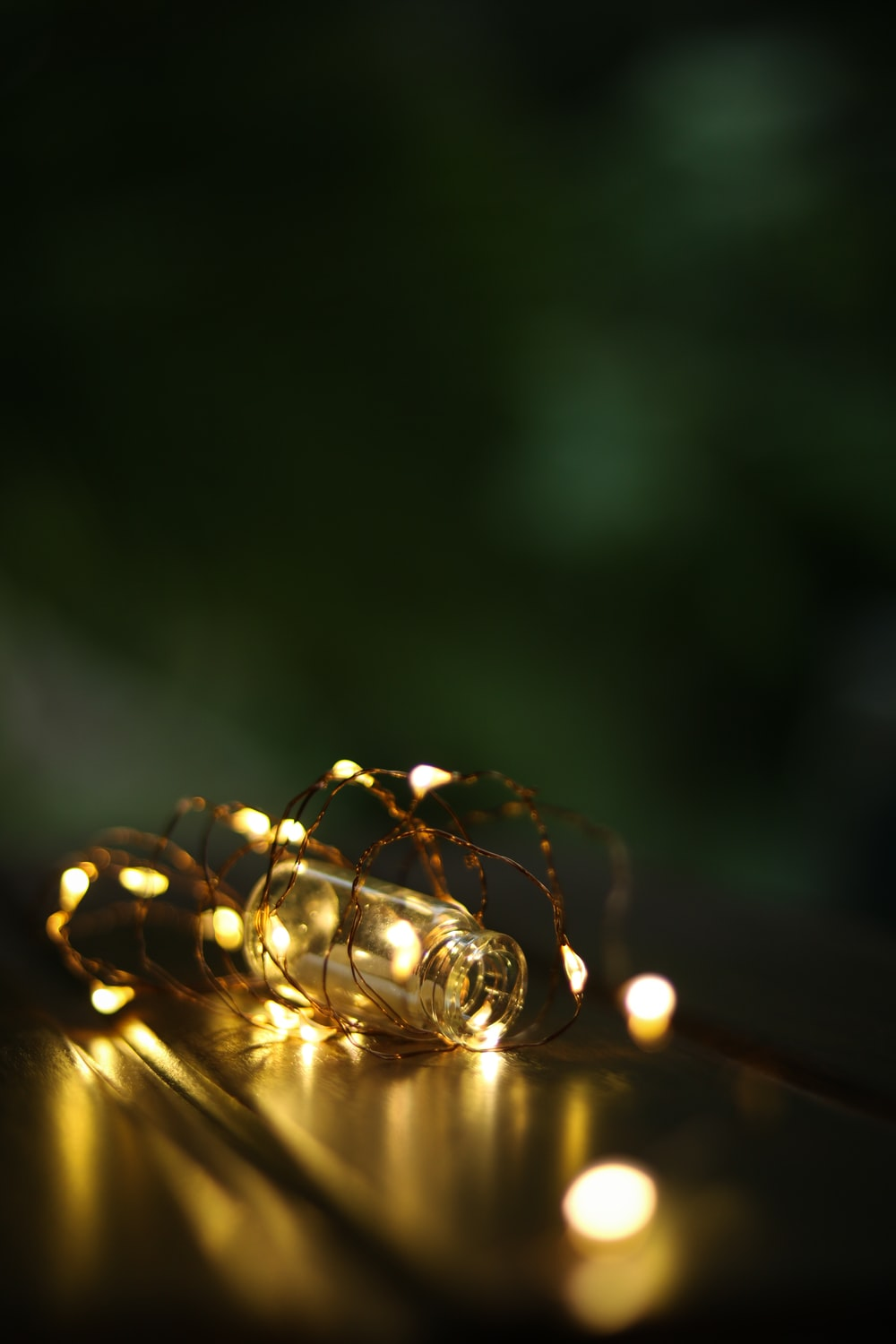 bokeh photography of yellow string lights and clear glass vial