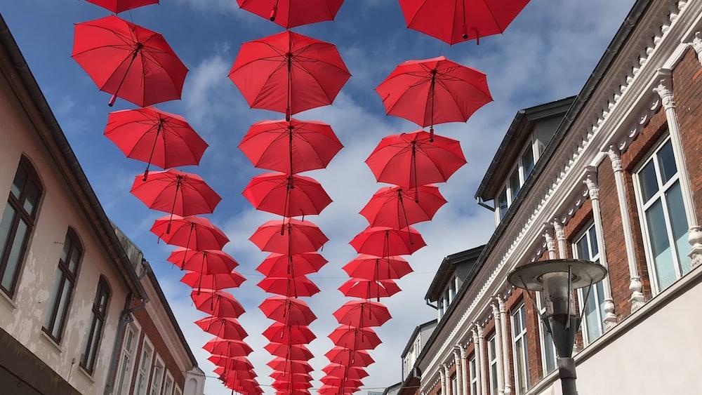 red umbrellas hanging on skies in between buildings