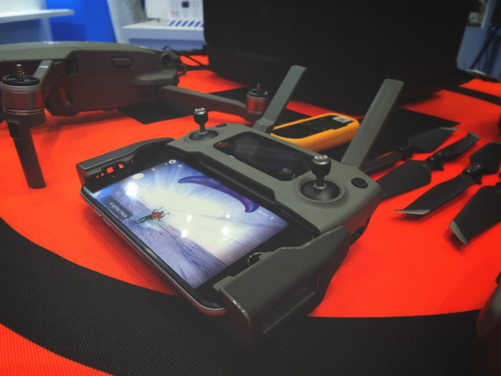 black game controller near gray drone