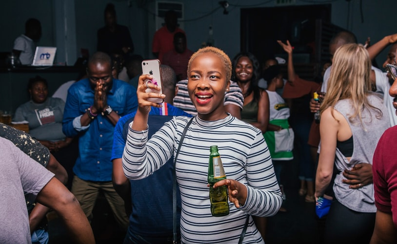 A photo of a black woman standing in a crowd at some kind of event - maybe a club - she is holding a drink in one hand and her phone in another