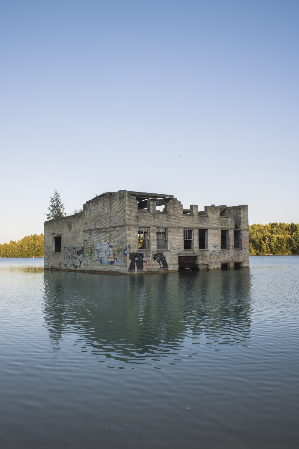 grey house ruins submerged in water under clear blue sky