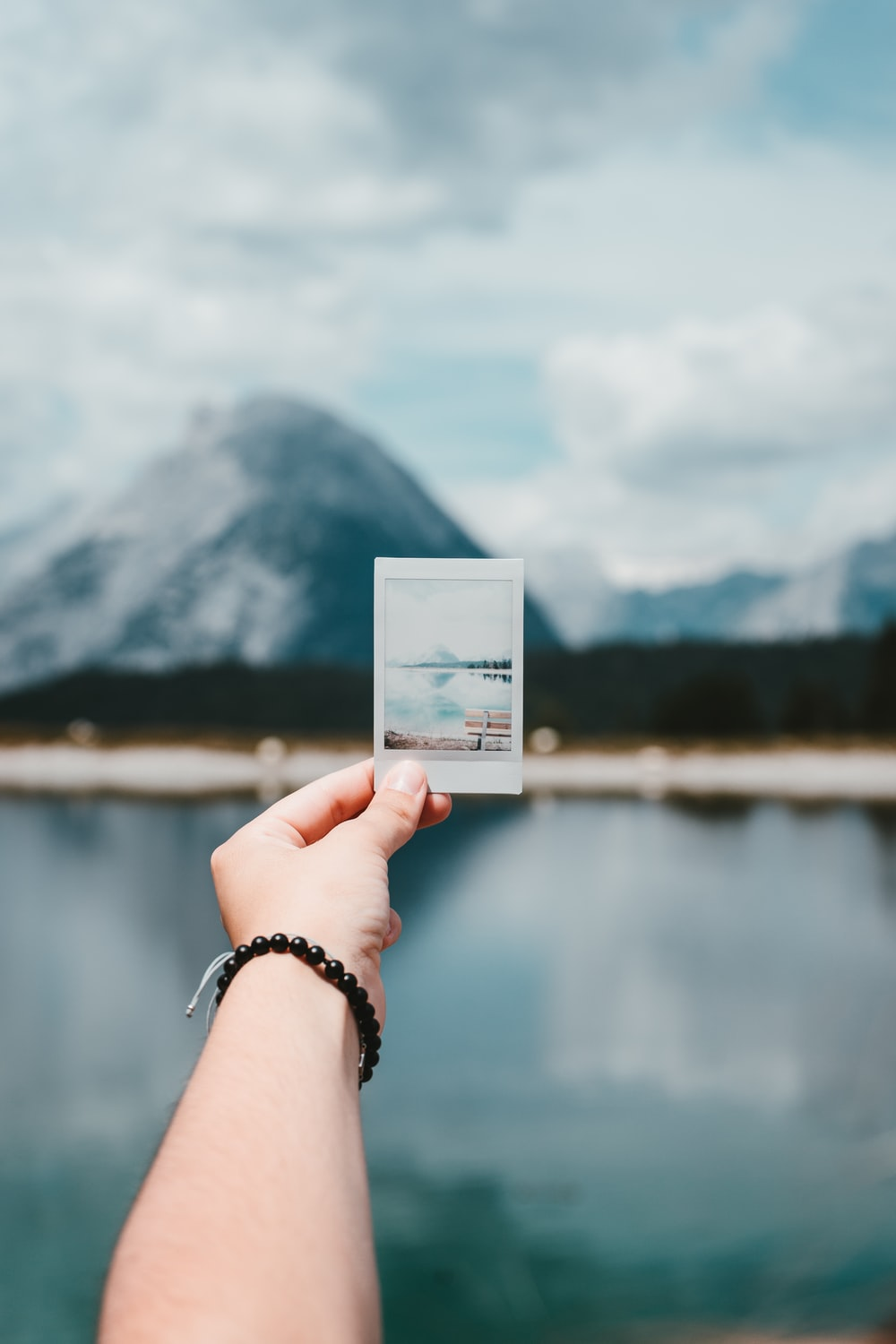 person holding photo of mountain
