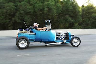 man riding hot rod on road