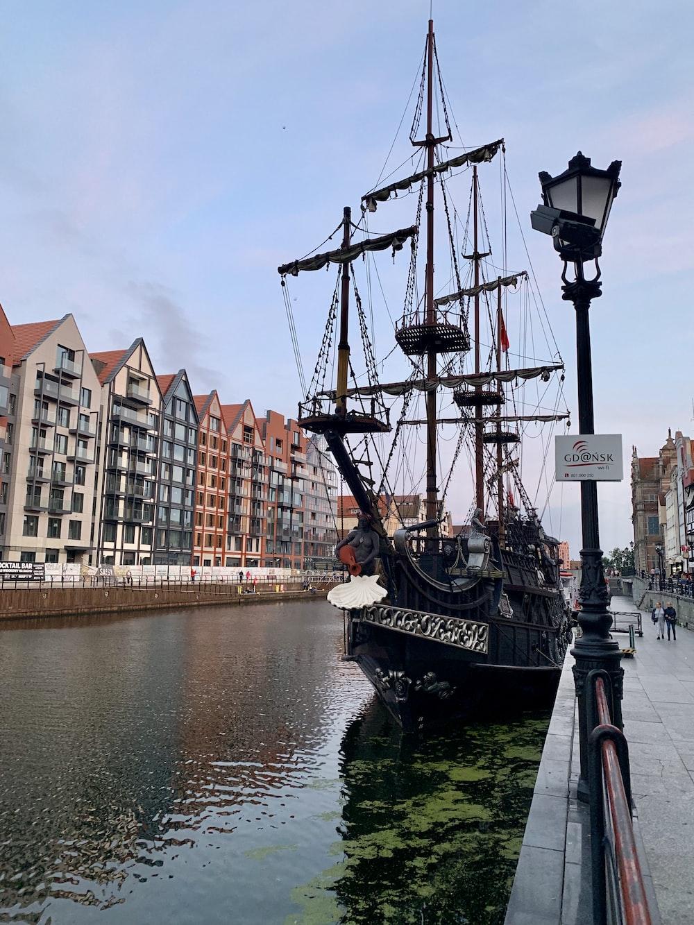 black galleon ship docked near houses during daytime