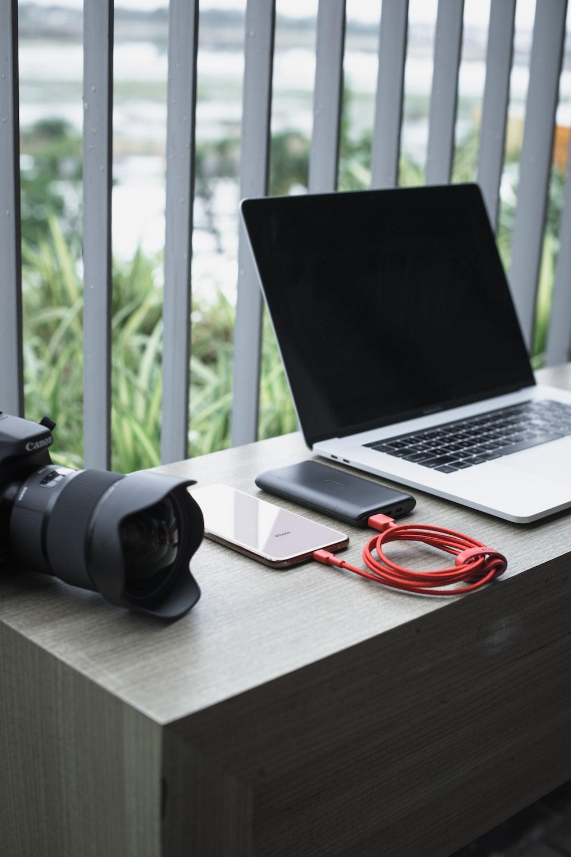 turned-off MacBook beside DSLR camera