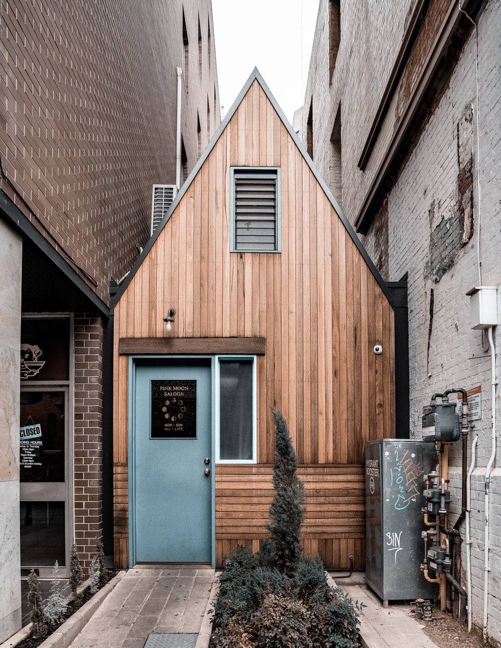 brown wooden house at the alley between buildings