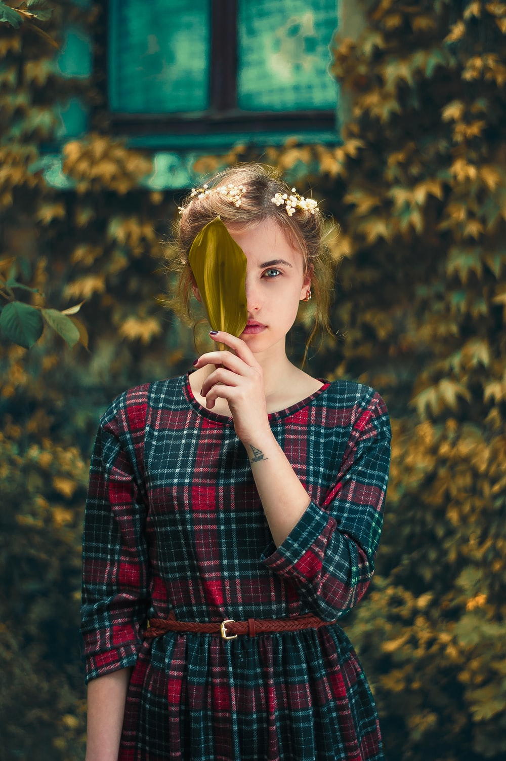 woman in green and red plaid dress standing and cover her right eye with green leaf