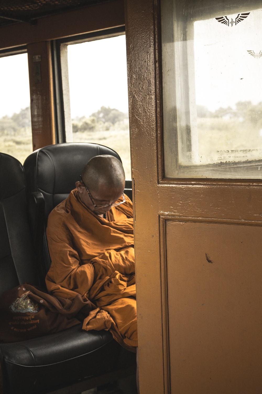 man sitting on black leather vehicle seat
