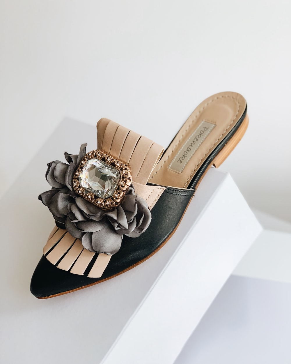 black and brown leather half shoe on white box
