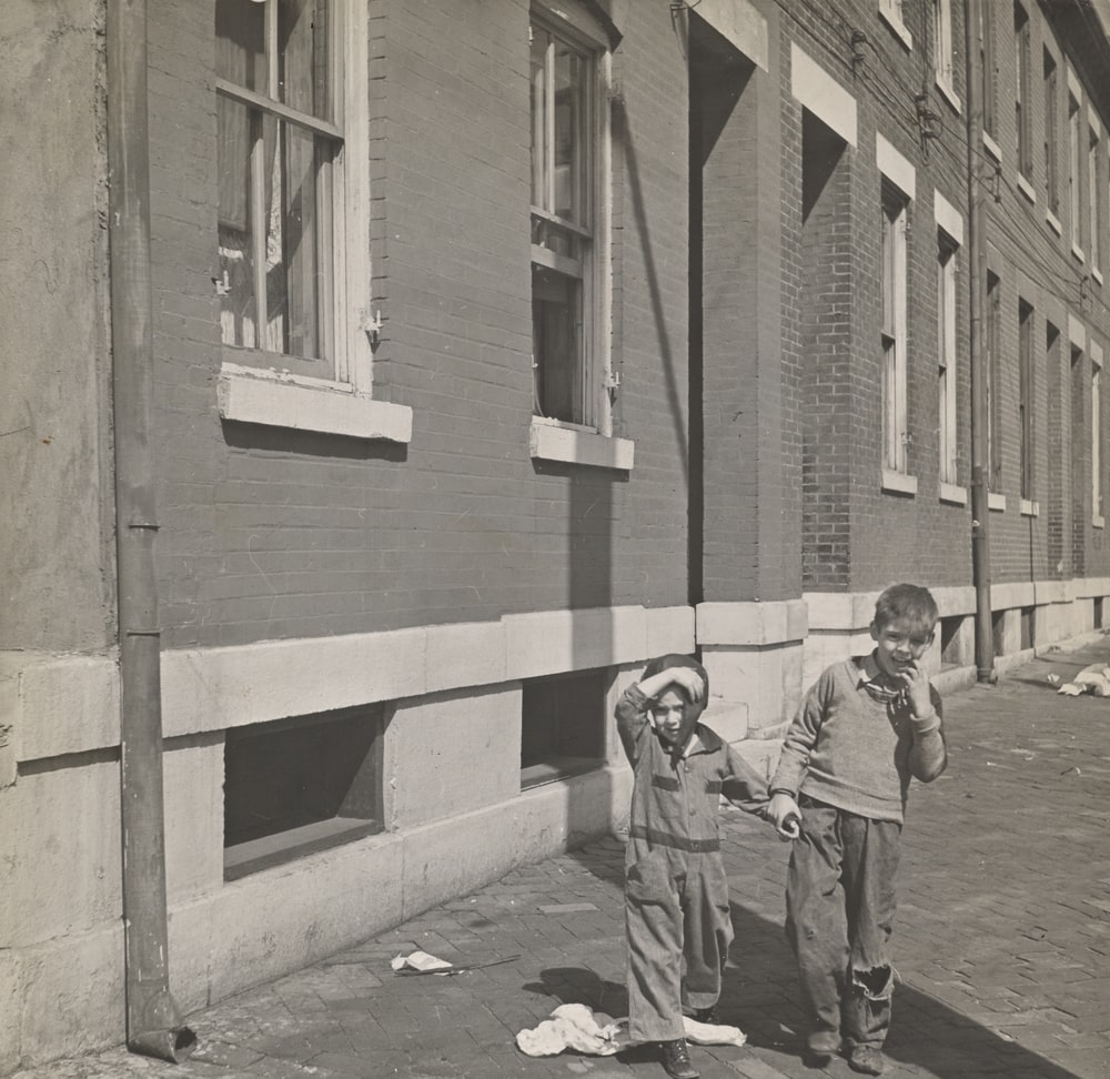 grayscale photography two toddlers standing outdoors