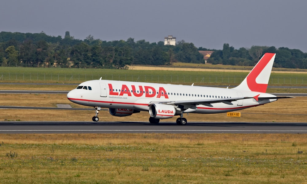 white and red Lauda airplane landing on railway