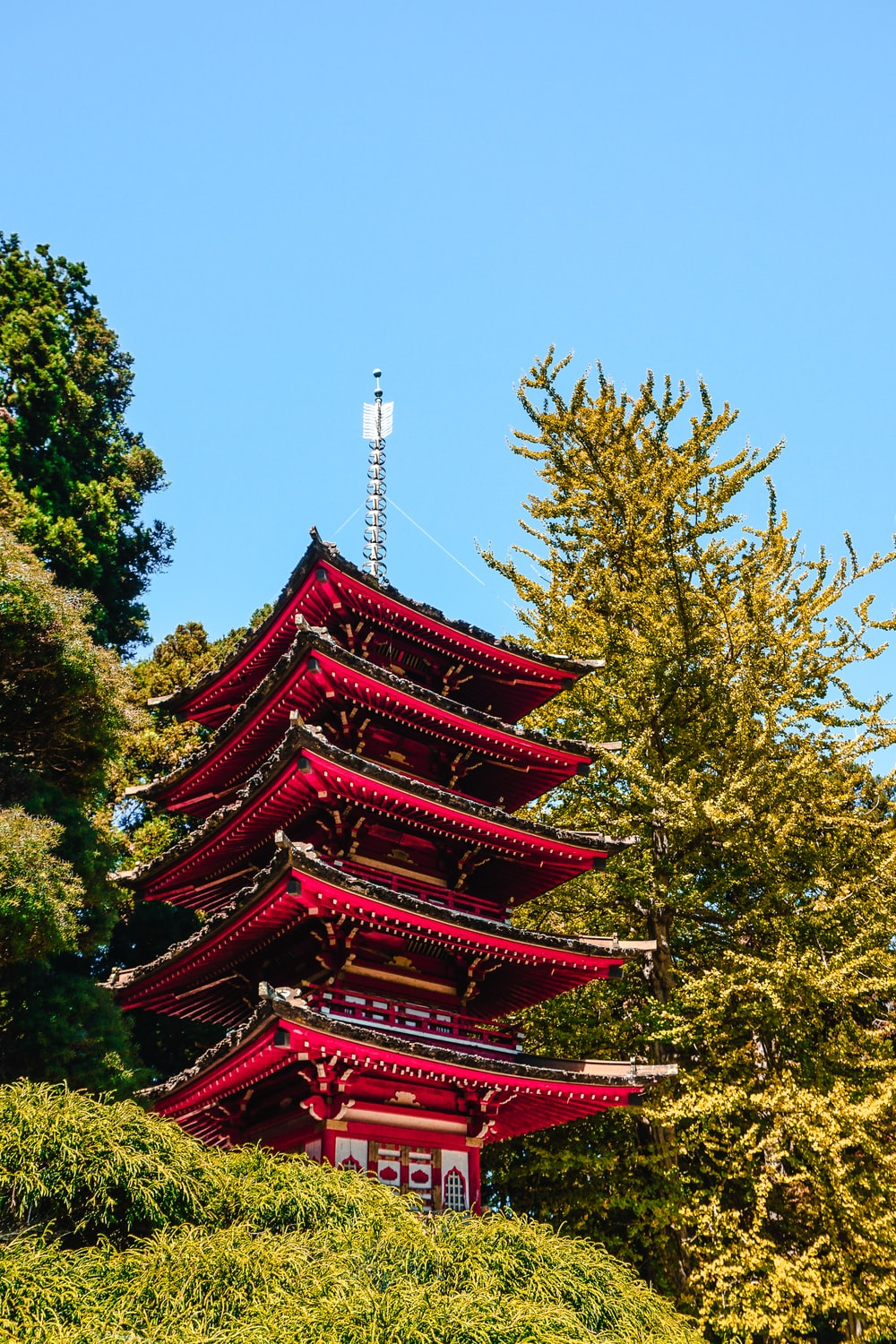 red and green multi-layer pagoda temple under calm blue sky