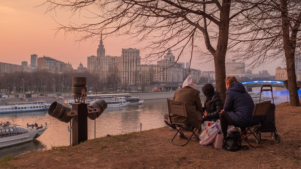 people sitting on bench near body of water during golden hour