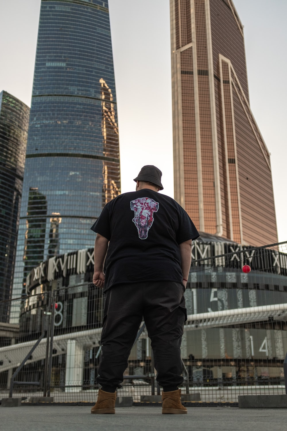man standing in front of high-rise glass buildings