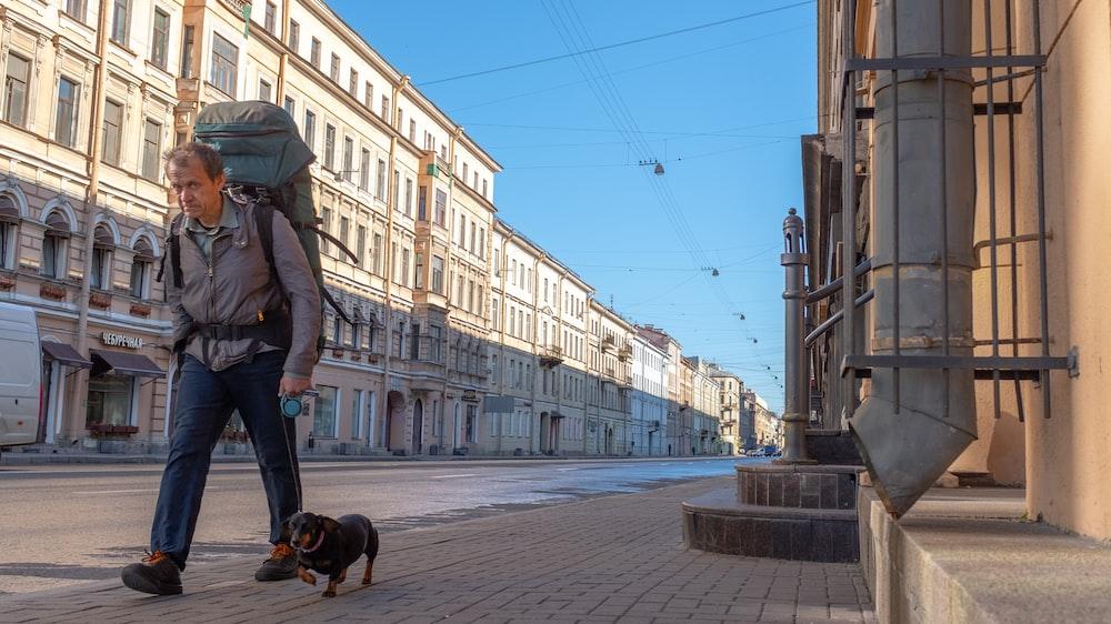 man walking beside dog
