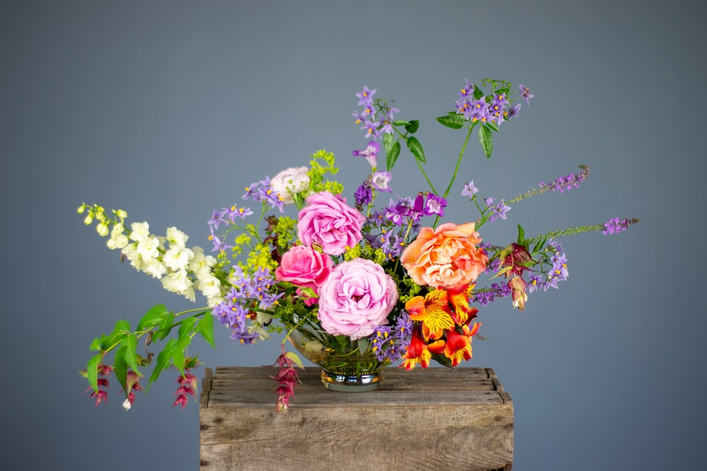 multicolored flowers in vase on wooden surface